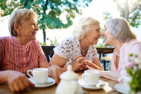 grannies: Cheerful grannies touching by noses and laughing