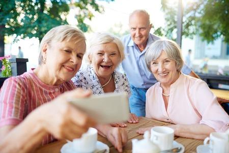 Šťastný senioři dělat selfie při zavěšení v venkovní kavárně