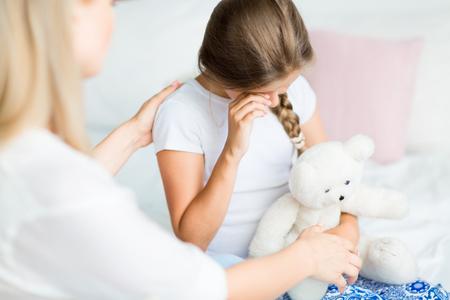 Little girl with teddy bear wiping tears