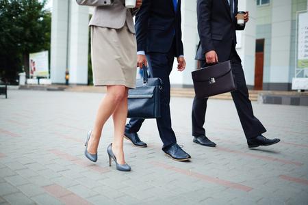 businesspeople: Group of elegant co-workers walking down street