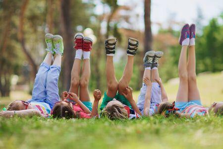 girl lying: Kids with raised legs lying in row