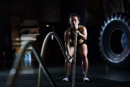 Mujer deportiva que practica ejercicio con la cuerda de batalla Foto de archivo