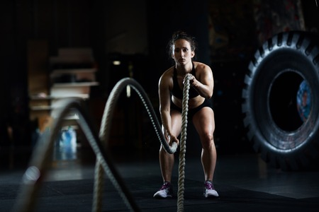 Sporty woman practicing exercise with battle rope