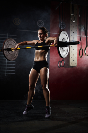 Strong young woman lifting heavy barbell