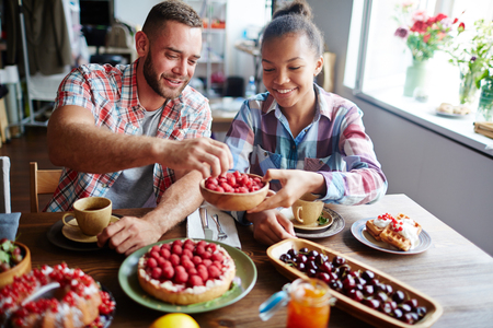Happy girl offering guy to take some fresh raspberries from bowl