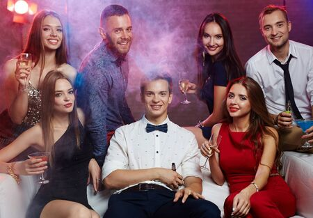 clubbers: Group of clubbers with drinks sitting in night club Stock Photo