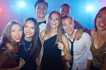 Ecstatic friends looking at camera in night club Фото со стока