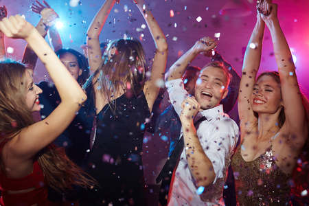 Amigos con las manos levantadas disfrutando de la noche en el club de baile Foto de archivo