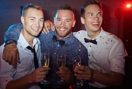 elegant party: Three elegant guys holding flutes with champagne