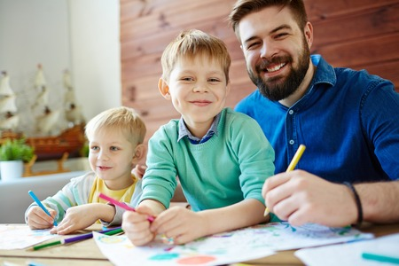 Happy father drawing together with his two sons