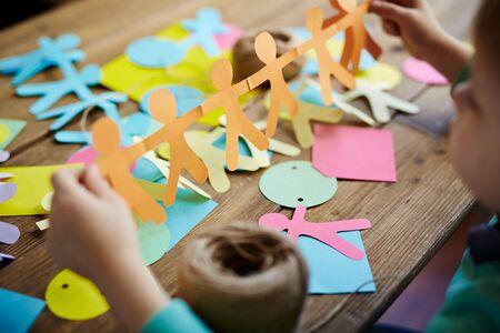 paper craft: Primer plano de niño pequeño que sostiene figuras de personas de papel