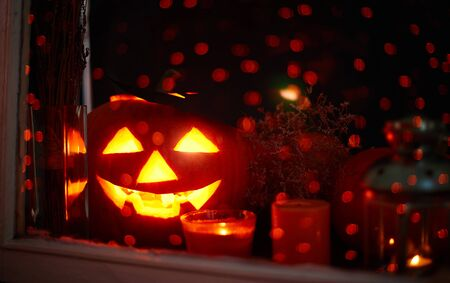 window sill: Jack o lantern glowing on window sill Stock Photo