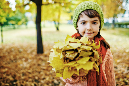 hazel eyes: Portrait of cute little brunette girl with hazel eyes holding big bunch of golden maple leaves, smiling and looking at camera in park on perfect sunny autumn day