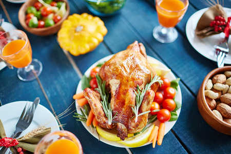 High angle view of rough wooden table filled with food and dishes, walnuts and pumpkin juice glasses, focus on big plate of homemade roasted chicken freshly out of oven, decorated with vegetables Stock Photo