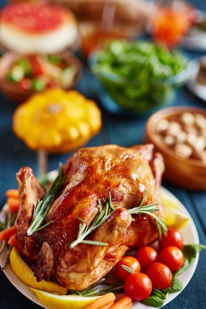Golden glistening roasted turkey decorated with vegetables and rosemary, on thanksgiving dinner table filled with dishes and food, pumpkin in background Stock Photo