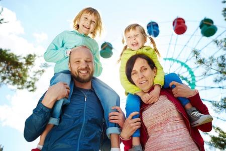 アミューズメント パーク、母と父の肩と暖かい秋の週末、バック グラウンドで観覧中にカメラ目線での二人の愛らしいブロンド女の子を運ぶ家族の