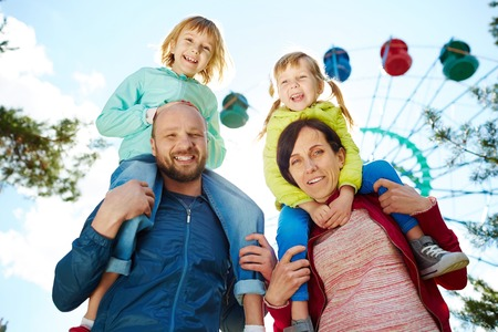 Low angle view of smiling family in amusement park, mother and father carrying their two adorable blond girls on shoulders and looking at camera during warm autumn weekend, ferris wheel in background Фото со стока - 62717537