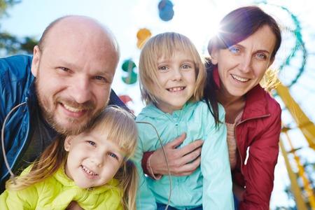 ダウン曲げカメラ目線の幸せな家族の肖像画、両親 2 人の美しい娘を抱いては、遊園地で一緒に週末の間に日光の下で閉じる