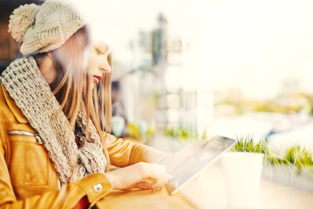 net surfing: Side view of young attractive girl wearing knitted hat and scarf sitting by window in cafe with tablet, surfing net, checking mail and social media, copy space to the right