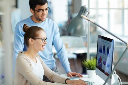 Twee jonge zakelijke collega's lachend en op zoek gelukkig als ze zien groeien financiële statistieken op het scherm van de desktop computer in een modern kantoor