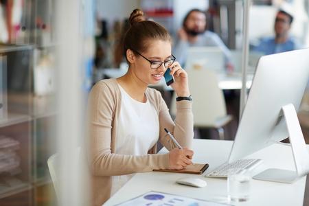 パートナーのモダンなオフィス空間におけるコンピューターの机に座って、小さなノートにメモを作っていると電話で話している広報で働く若いプ