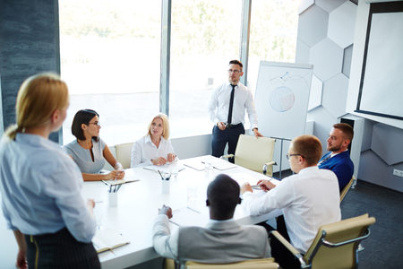 proficient: Large group of business partners interacting at seminar Stock Photo