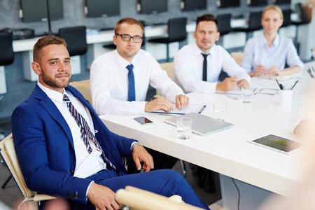 personas escuchando: Hombres de negocios que escuchan la presentación Foto de archivo