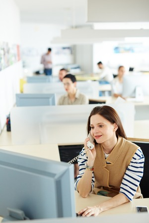 openspace: Pretty secretary calling in front of laptop in open-space office