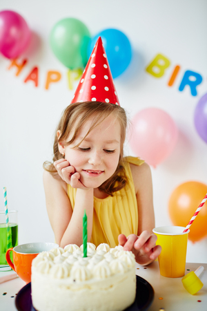 sweettooth: Adorable girl tasting birthday cake with whipped cream