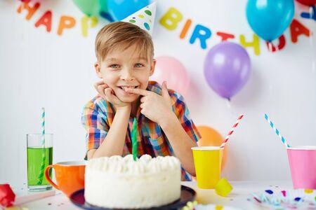 Netter Junge Verkostung leckerer Nachtisch Geburtstag Standard-Bild