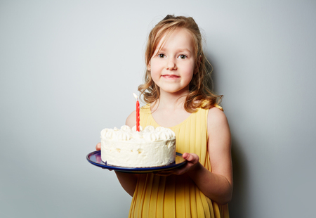 sweettooth: Pretty youngster holding birthday cake with whipped cream