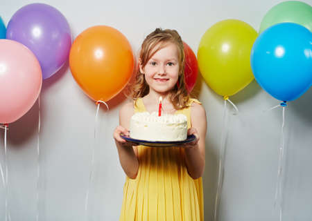 sweettooth: Pretty little girl with birthday cake and balloons Stock Photo