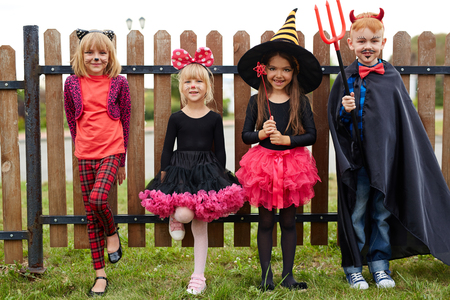 Halloween kids in costumes looking at camera Stock Photo