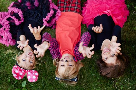 Three girls with frightening expression lying on grass Stock Photo