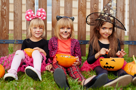 wooden fence: Friendly Halloween girls sitting on grass against wooden fence