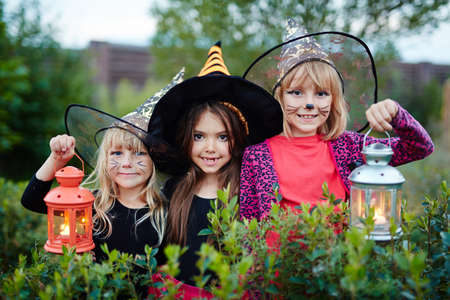 repent: Halloween girls with lanterns looking at camera in garden Stock Photo