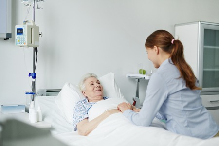 ward: Aged woman looking at her granddaughter in ward