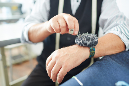 selfemployed: Hands of tailor with needle-case during work Stock Photo