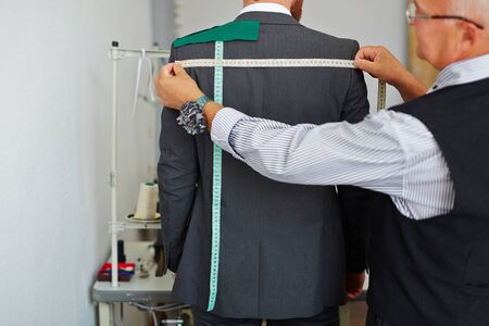 tailor measure: Tailor measuring back width of male jacket