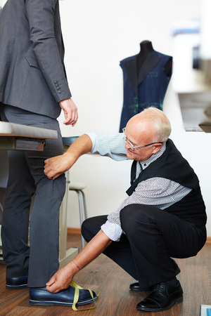 tailor measure: Tailor going to measure trousers