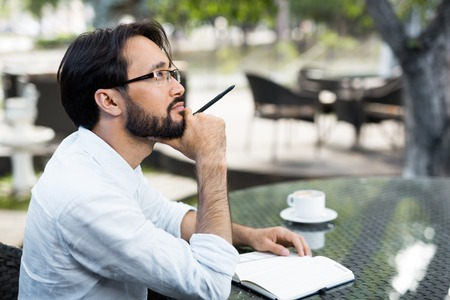 Inspired Asian man sitting in outdoor cafe Stock Photo