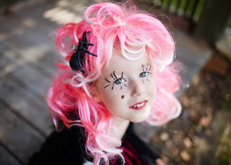 Cute little girl in pink wig looking at camera Stock Photo