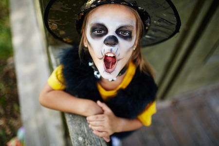 attire: Little girl with frightening expression wearing Halloween attire