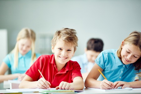 Happy schoolboy looking at camera at lecture photo