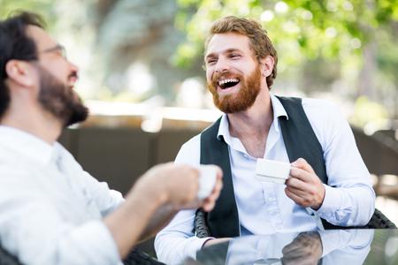 Vriendelijke jonge mannen met koffie praten in de buitenlucht cafe Stockfoto