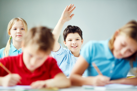 Happy boy raising hand at lesson to ask question photo