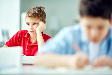 reluctant: Bored schoolboy sitting at lesson Stock Photo