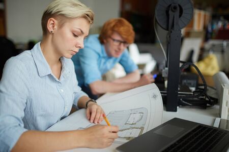 Working Environment: Young businesswoman drawing sketch in working environment Stock Photo