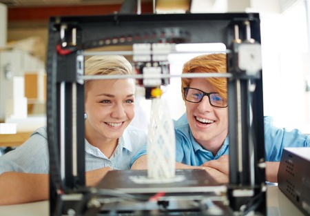 Two happy engineers looking at architectural model in 3d printer