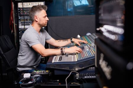 adjusting: Modern man adjusting sound in audio studio Stock Photo
